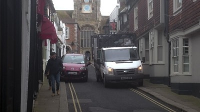 A car is forced up on the pavement in order to pass a parked lorry, and the pedestrians are unaware of the danger behind them.